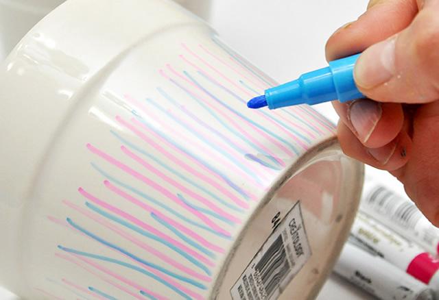 Faça listras com o marcador azul no pote de cerâmica